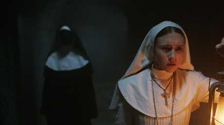 Taissa Farmiga as Sister Irene (foreground) in a scene from film The Nun