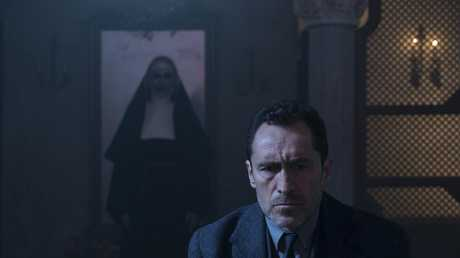 (L-R) BONNIE AARONS as The Nun and DEMIAN BICHIR as Father Burke in a scene from New Line Cinema's horror film