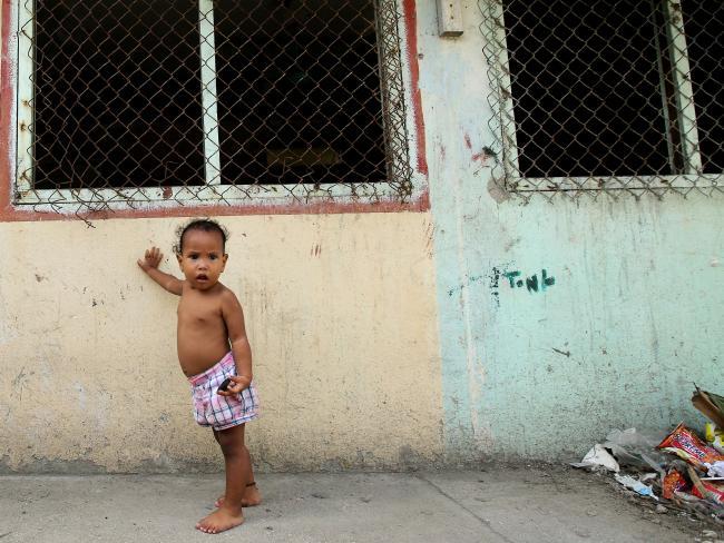 Children wander around streets strewn with rubbish.