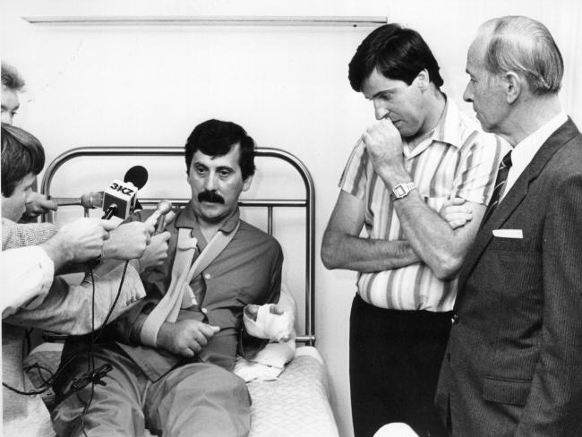 """Det-Sgt John Kapetanovski (left) being interviewed by the media in 1986 after being shot and wounded by Noble Park gunman Pavel """"Mad Max"""" Marinof. His police partner Sgt Rod MacDonald (middle) and the then Victoria Police Chief Commissioner Mick Miller (right) were visiting him in hospital. Sgt MacDonald shot and killed Marinof during the gunbattle in which he and Det-Sgt Kapetanovski were wounde"""