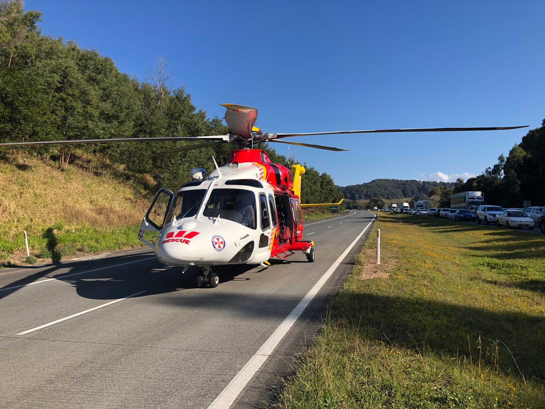 The Westpac Life Saver Rescue Helicopter lands on the Pacific Highway near Pottsville to transport patients after a crash.