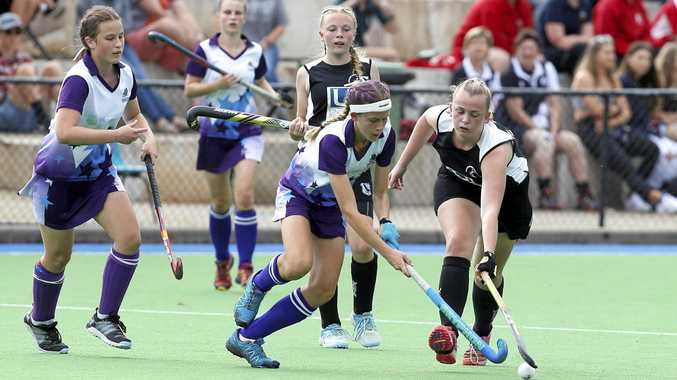 STICKING TO IT: Determined players from Thistles and Wests battle for the ball during Saturday's thrilling afternoon of junior grand finals at the Ipswich Hockey Complex. Thistles held out Wests 1-0 in the C-Grade grand final. Wests won two premierships early in the day with Hancocks, Easts and Norths also enjoying grand final success.