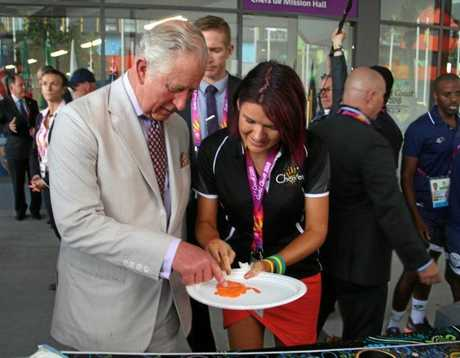 Chern'ee Sutton adds Prince Charles's fingerprint to her artwork at this year's Commonwealth Games.