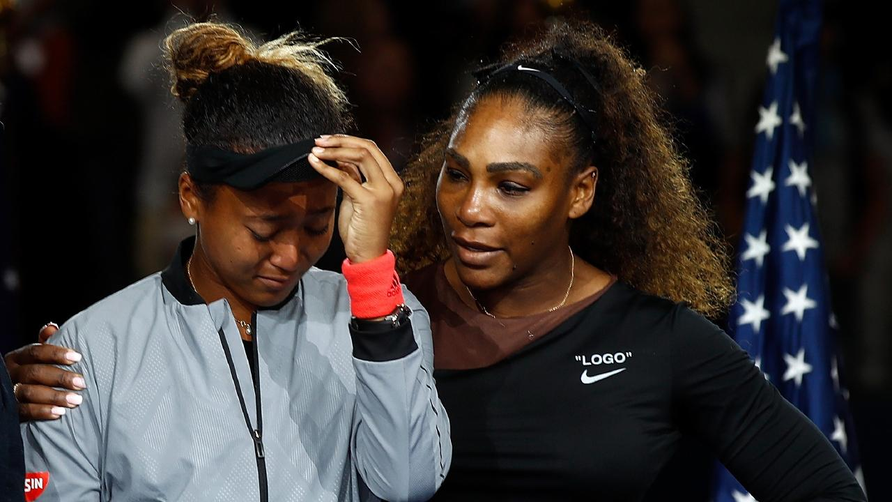 Serena Williams puts an arm around Naomi Osaka at the trophy ceremony.