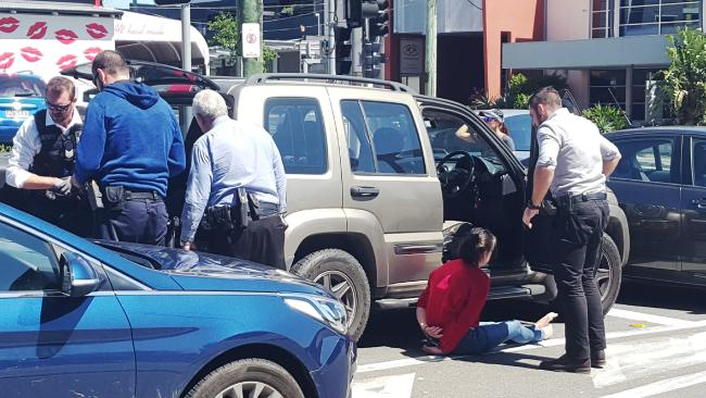 Police search a vehicle and have two people in handcuffs and the cnr of Mayne Road and Campbell Street Bowen Hills. Photo Michael Ross