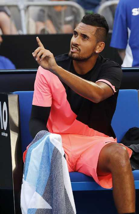 Nick Kyrgios talks with the chair umpire between games after receiving a code violation for telling a spectator to shut up at the Australian Open. Picture: Michael Klein