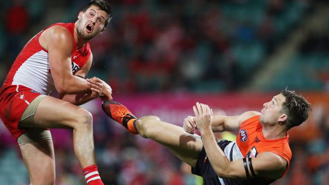Toby Greene kicks Sydney's Nic Newman while trying to take a mark. Picture: Phil Hillyard