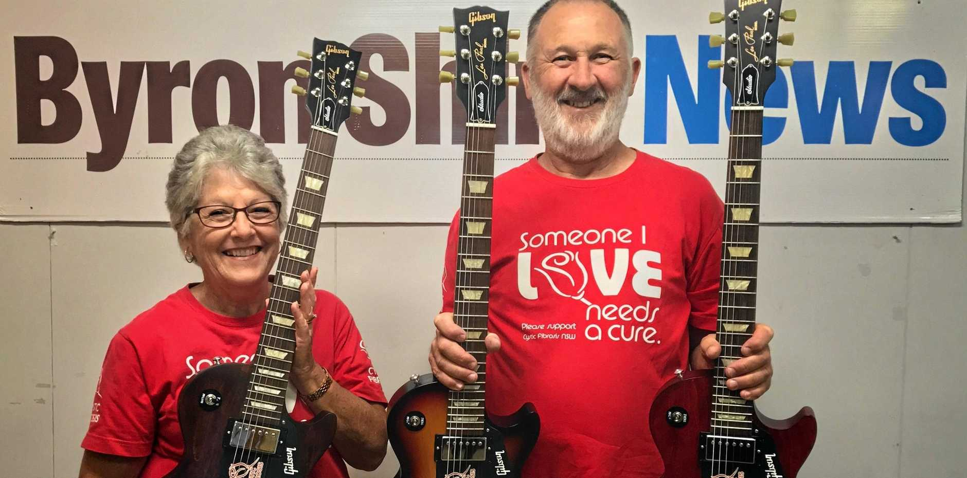 CAMPAIGNERS: Jenny and Alan Tunks on the fundraising trail with Gibson guitars they raffle at Bluesfest each year to raise money for research into a cure for cystic fibrosis.