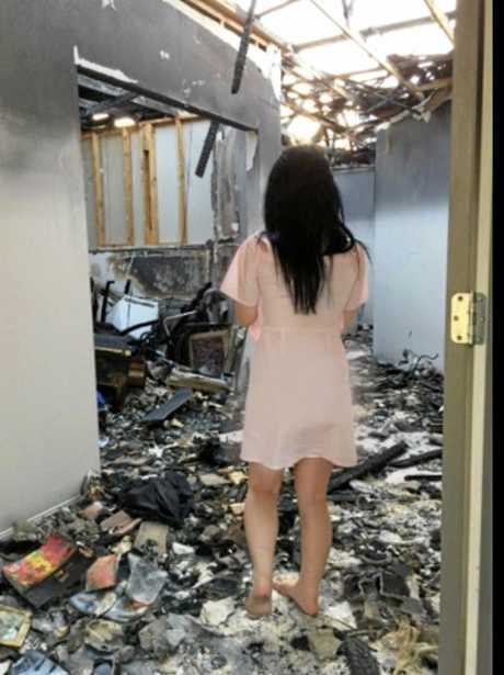 April Wilmot walks through what's left of her family home a week after the fire.
