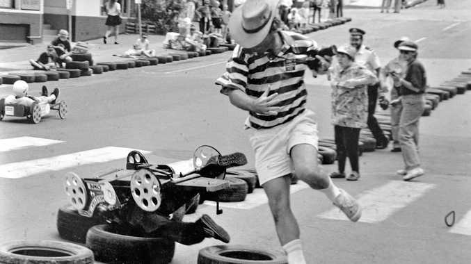 FROM THE 1990s: Gympie Times photographer Tony Watson leaps out of the way as a entrant in Gympie's annual Gold Rush Festival billy cart race crashes in Monkland St, near the Nash St intersection, after losing a tyre, in the early 1990s. Gympie black and white photographic enthusiast Max Krough took this amazing action picture of the instant of disaster, with the tyre that caused the crash still rolling along the road on the lower right side of the photograph and Mr Watson still in the air as he jumped out of the way.