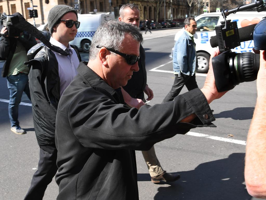 A supporter pushes away camera outside court. Photo: AAP