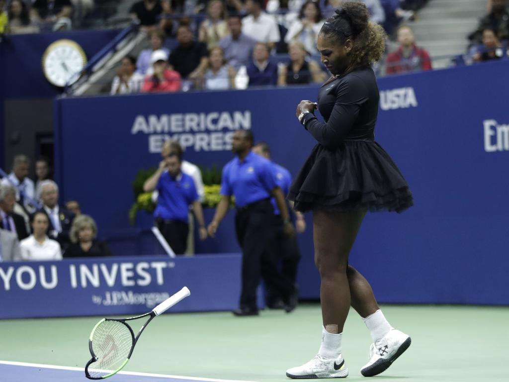 Serena Williams slams her racket on the court. (AP Photo/Julio Cortez)