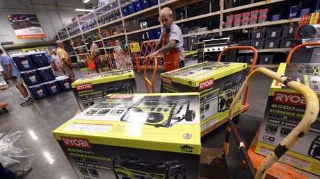 Home Depot employee prepares more generators for sale.