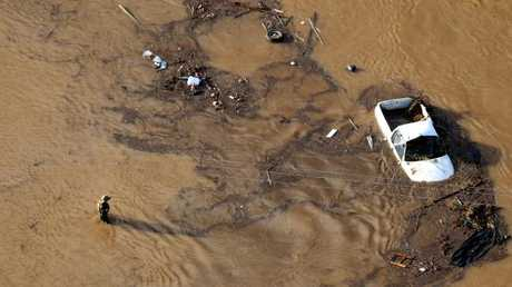 Police officers search the wreckage after severe floods hit Grantham in the Lockyer Valley, Queensland.