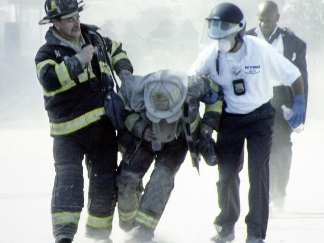 There were many moments amid the horror of that day that demonstrated love and kindness. Firefighter Louie Cacchioli, left, helping a fire chief after the towers collapsed.