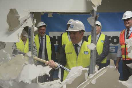 SMASHING: Consolidated Properties Group executive director Don O'Rorke takes a sledgehammer through a wall to signal the start of the Wilsonton Shopping Centre redevelopment.