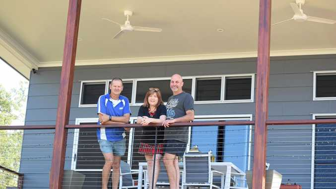 HOME SWEET HOME: Mark Postle from Possco with proud home owners Rebecca and Scott Wicks on the veranda of their award-winning home.