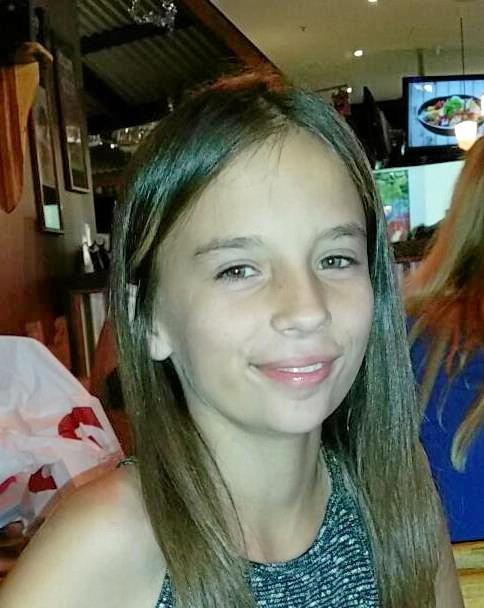 Jessica Moore has long blonde/brown hair, hazel eyes and fair skin.