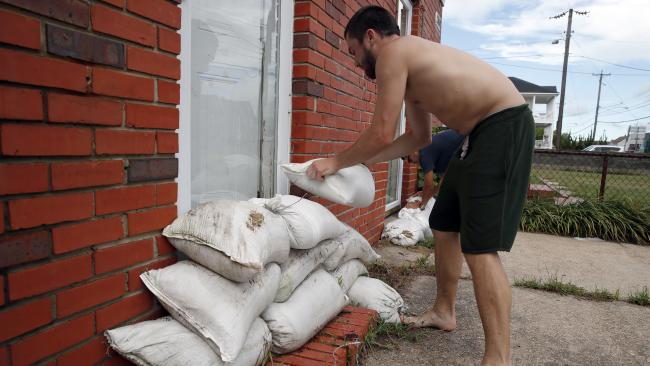 Adam Bazemore places sandbags in the doorways in the Willoughby Spit area of Norfolk, Virginia. Picture: AP