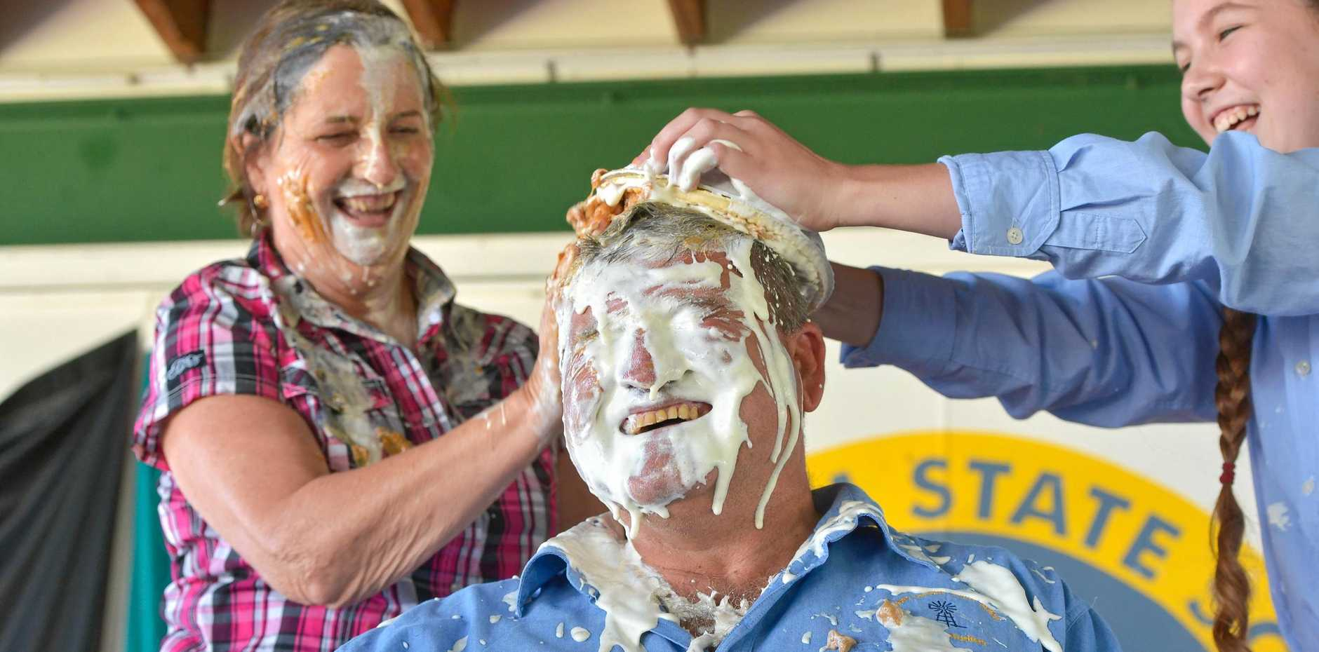 CREAMED: Mt Larcom State School principal Pauline Porch and student Shalom White have a laugh as teacher Norm Horan cops a caramel cream pie in the face. The school helped raise money for drought relief.