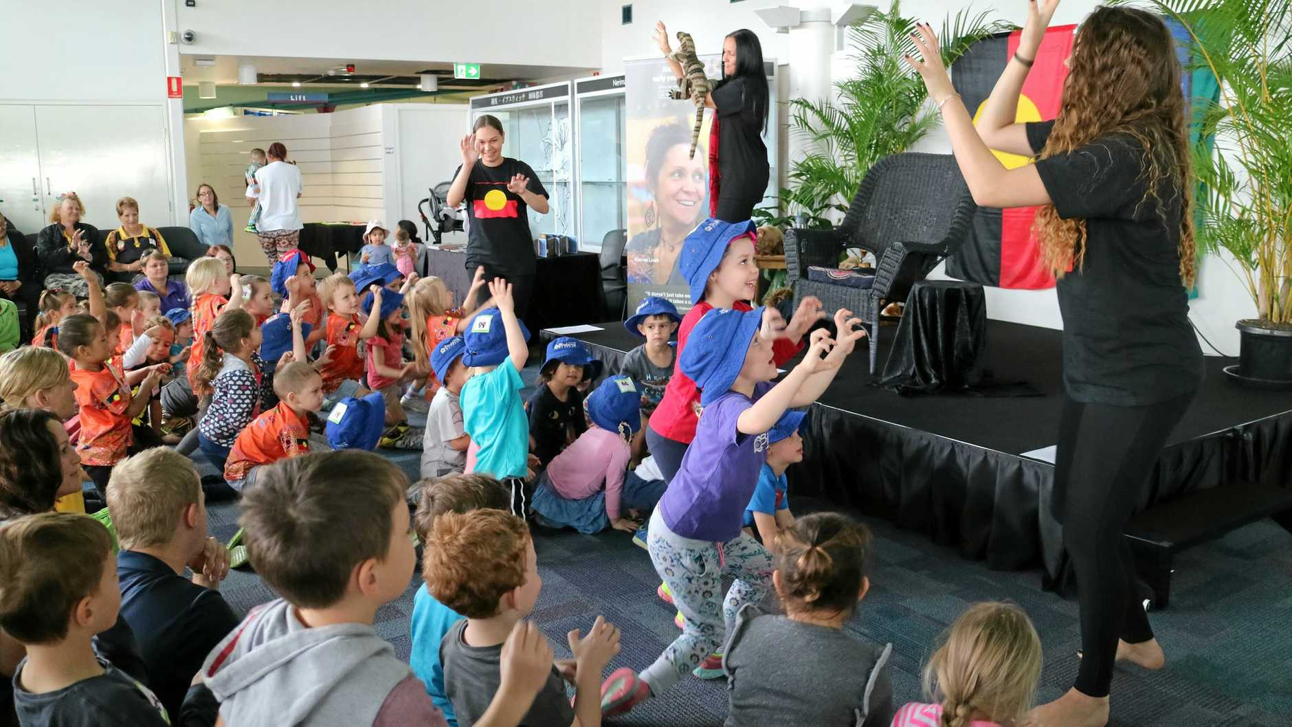 Aunty Sharron Lindh (on stage) with her daughter Jessica Midgely (right) and niece Tianhi Boschman (left) singing to the children at Ipswich Central Library.