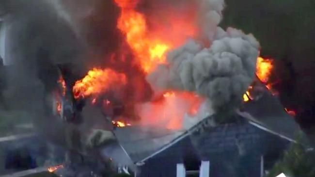 Flames consume a home in Lawrence, Mass, a suburb of Boston. Picture: WCVB