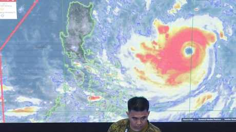 A member of the Philippine air force stands in front of a satellite image of Typhoon Mangkhut. Picture: Aaron Favila/AP