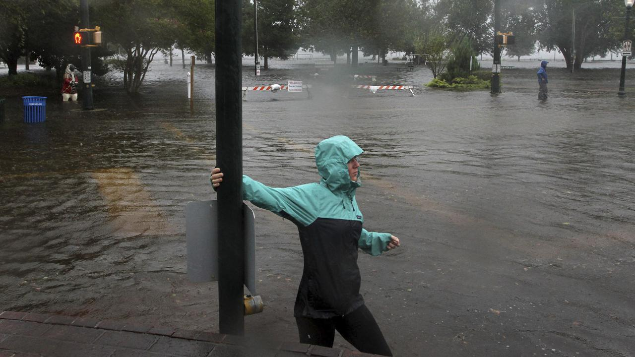 Jamie Thompson walks through flooded sections of East Front Street near Union Point Park in New Bern, North Carolina on Thursday, Sept. 13, 2018. Picture: Gray Whitley/Sun Journal via AP