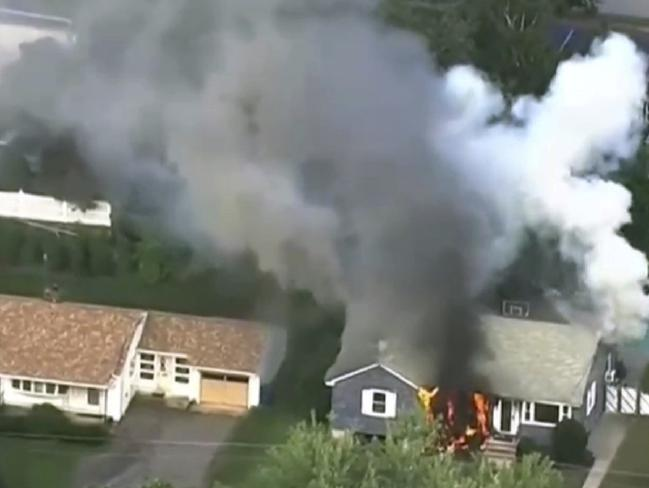 Flames rise from a house in Lawrence, Mass, a suburb of Boston, Picture: WCVB