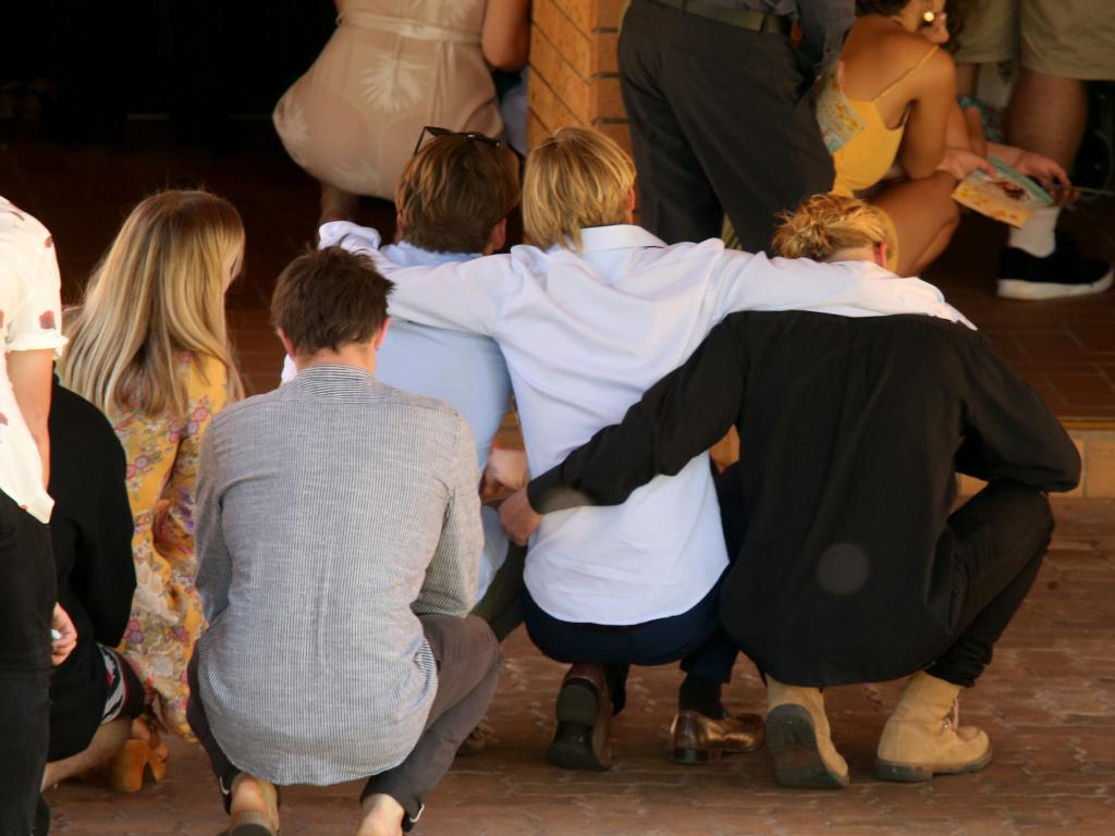 Mourners crouch together on the ground, clinging to one another in their grief. Picture: Nathan Edwards