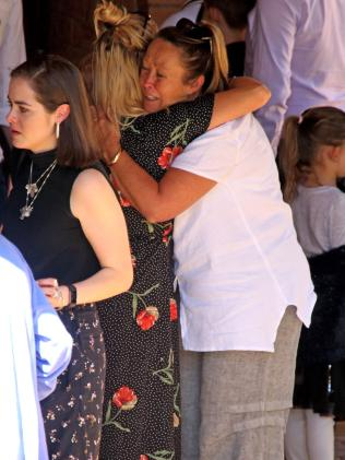 Sinead's mother, Kylie McNamara, dressed in a white shirt, hugs her daughter's friend. Picture: Nathan Edwards