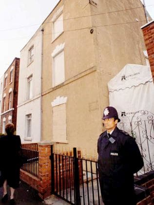 A police officer stands guard at 25 Cromwell St, Gloucester. The house has since been demolished.