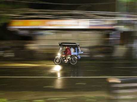 A man rides his tricycle as strong winds and rain from Typhoon Mangkhut. Picture: Aaron Favila