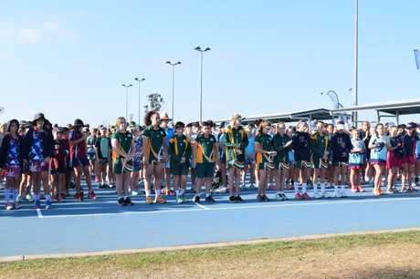 More than 1500 Queensland primary school netball players, officials, organisers and parents stood in silence this morning to commemorate the death of an 8-year-old Coomera Netball Club member who was one of two people killed in a head-on crash on the Bruce Highway near Childers on Friday.