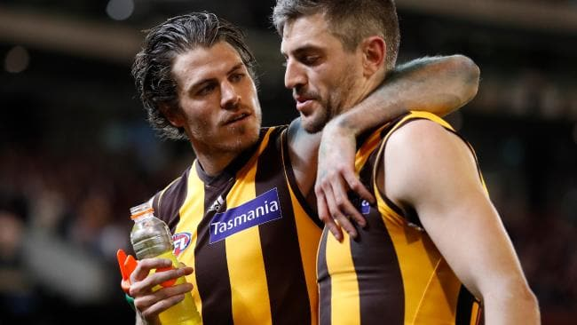 Isaac Smith, pictured consoling Ricky Henderson, has become one of the Hawks' strongest leaders. Picture: AFL Media/Getty Images