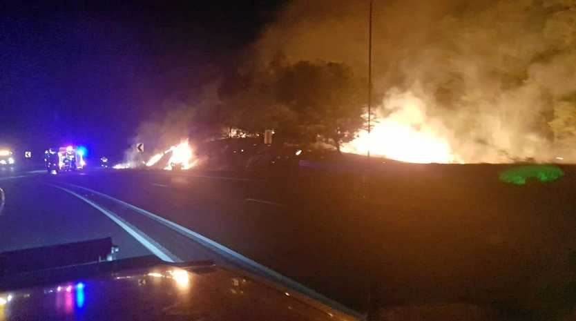 Emergency services on scene of a single-vehicle crash and car fire which spread to nearby bushland this monring.