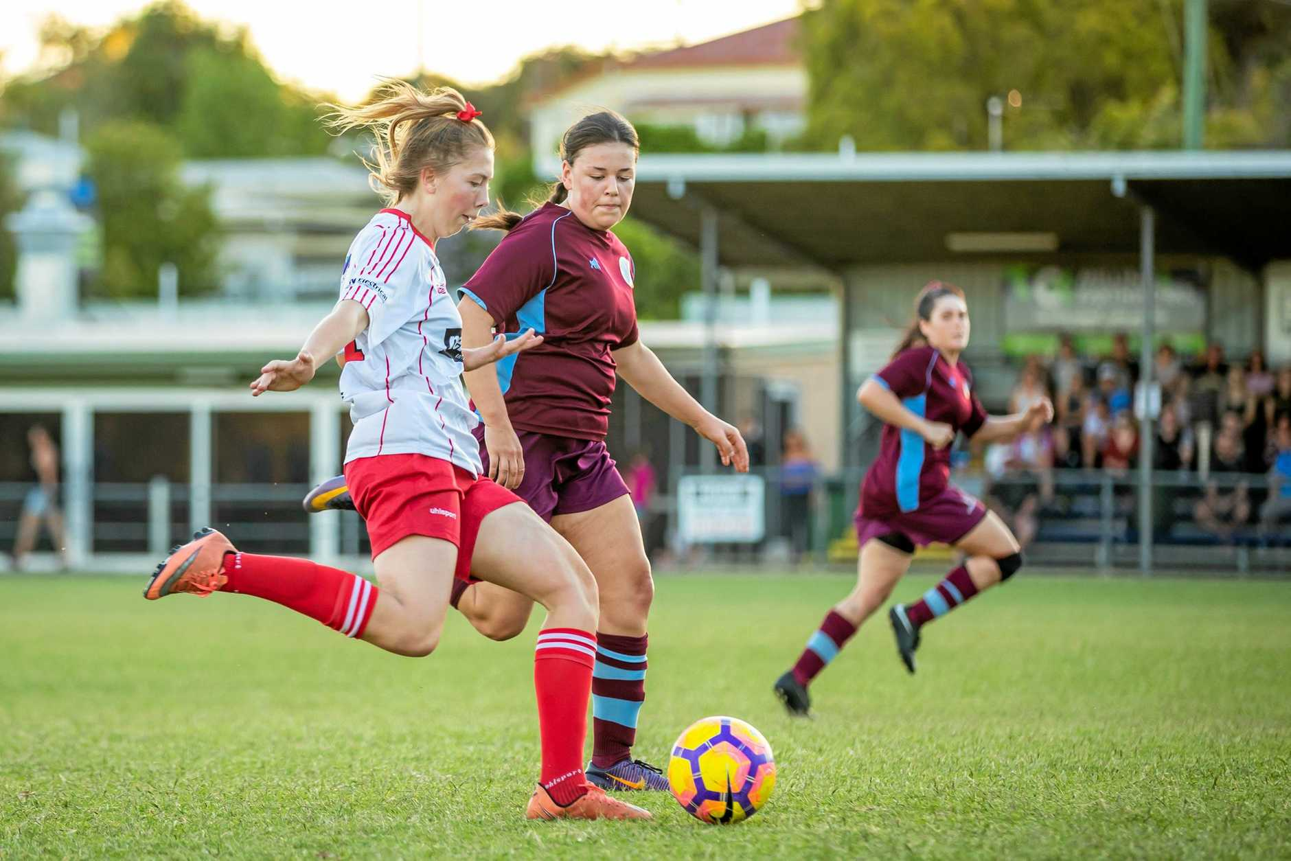 KEEN EYE: Lions Emma Kraak moves the ball up the field despite the Diggers maroons' defence.