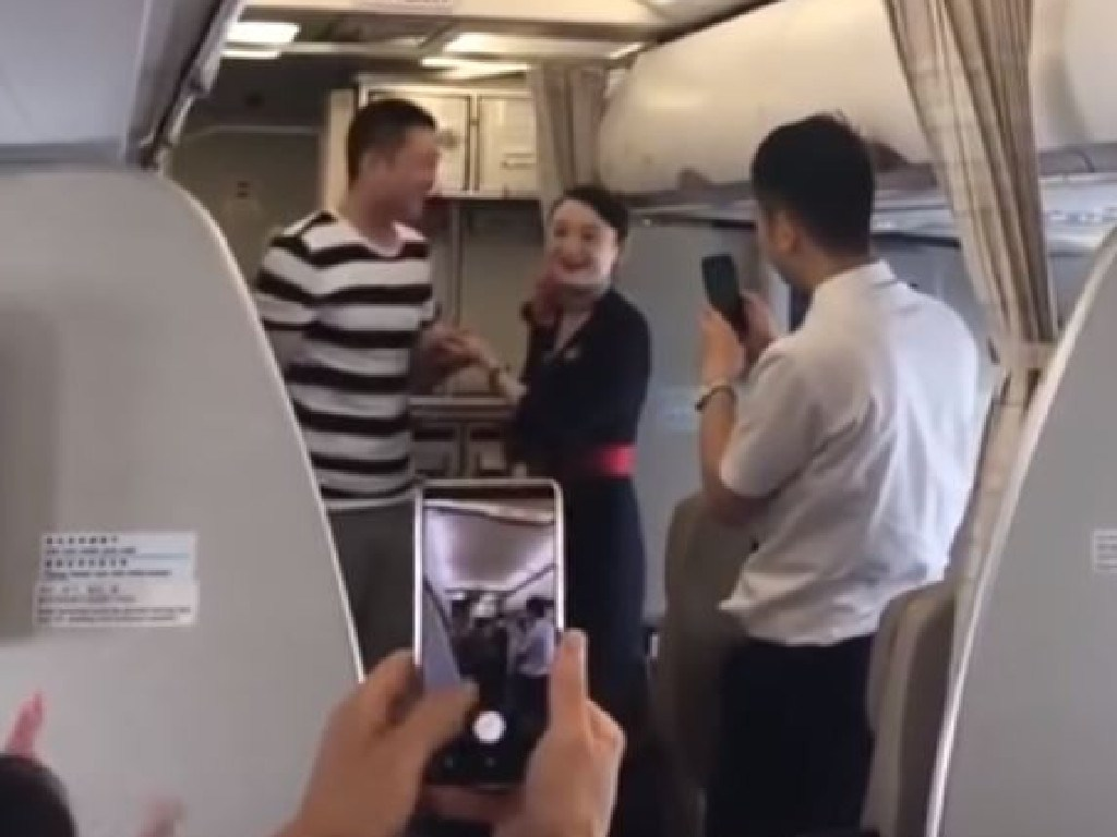 The happy couple deliver the news to cheering passengers. Picture: YouTube