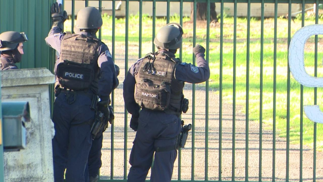 Police surround the clubhouse at Horsley Park before a man surrendered.