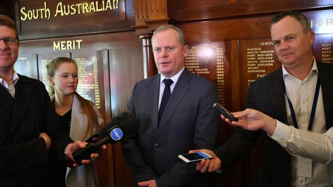South Australian National Football League chief executive Jake Parkinson (centre) speaks to the media at Adelaide Oval on Tuesday. Picture: David Mariuz/AAP