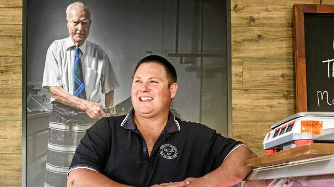 KEEPING WATCH: The Fair Butcher Maclean owner Chris O'Connor with a picture of the former owner of the RP Walters Butcher site, Sid Jones, over his shoulder.