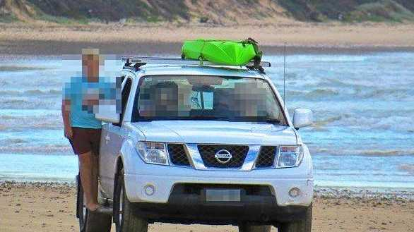 A car photographed on Brooms Head beach with children hanging out the window and sitting in the front seat.