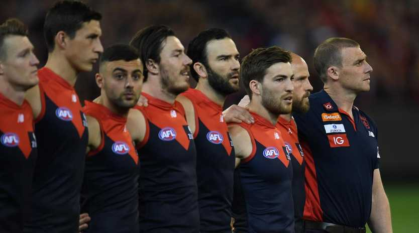 Demons coach Simon Goodwin (right) is seen alongside his players during the national anthem. (AAP Image/Julian Smith)