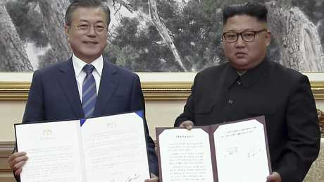 In this image made from video provided by Korea Broadcasting System (KBS), the two leaders pose after signing documents in Pyongyang.