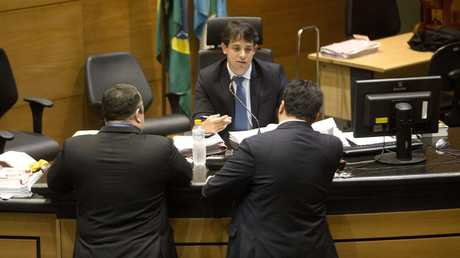 Brazilian judge Daniel Werneck Cotta talks with lawyers before the start of a pre-trial hearing of Mario Marcelo Santoro at a Rio de Janeiro court.