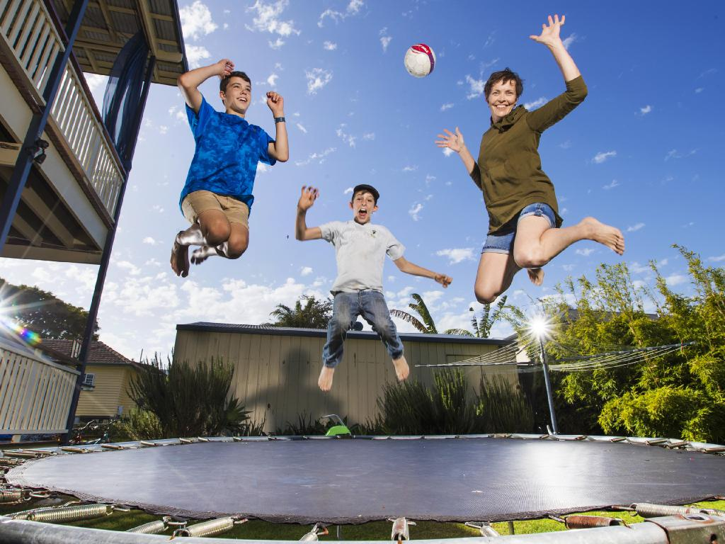 Eli, 12, Noah, 9, with Mum Madeline Avci keep active on the backyard trampoline. Picture: Nigel Hallett