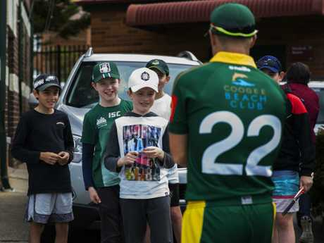 David Warner signs autographs for young fans.