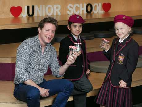 Scott Pape, The Barefoot Investor is pictured at Haileybury School in Melbourne with  Ruby and Abdul and their money jars. Picture: Ian Currie