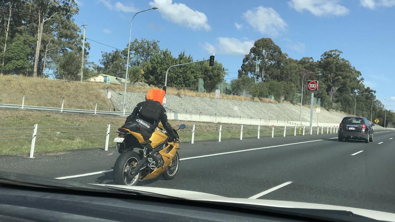 A motorcycle rider caught during a risky stunt at 100km/h on the Bruce Highway.