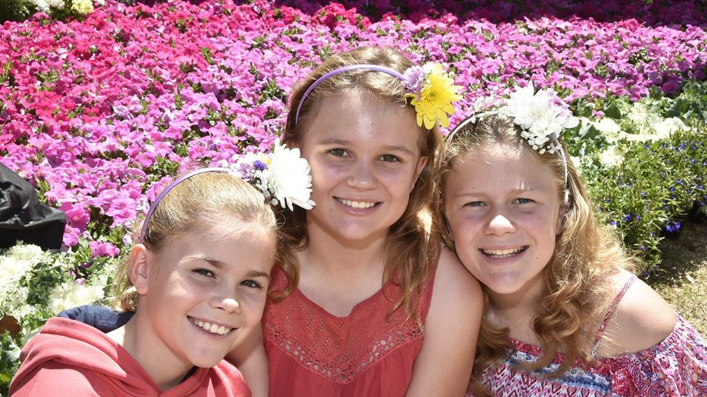 Pretty as the petals in the background, sisters from left; Megan, Natalie and Elise Hoppe. Food & Wine Festival in Queens Park. Carnival of Flowers, September 2018